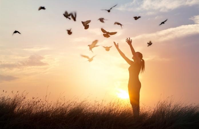 hopeful woman releasing birds in a meadow