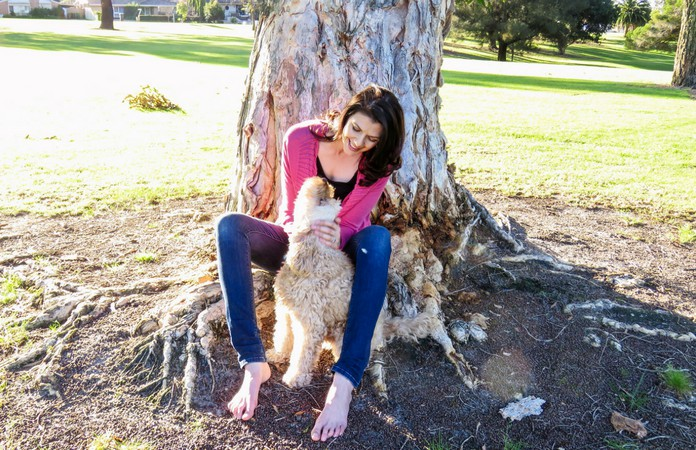 Linda Cull sitting by a tree and patting her dog Harry