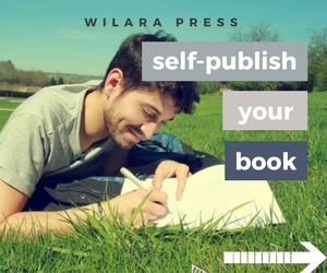 Smiling man lying on grass writing in notebook