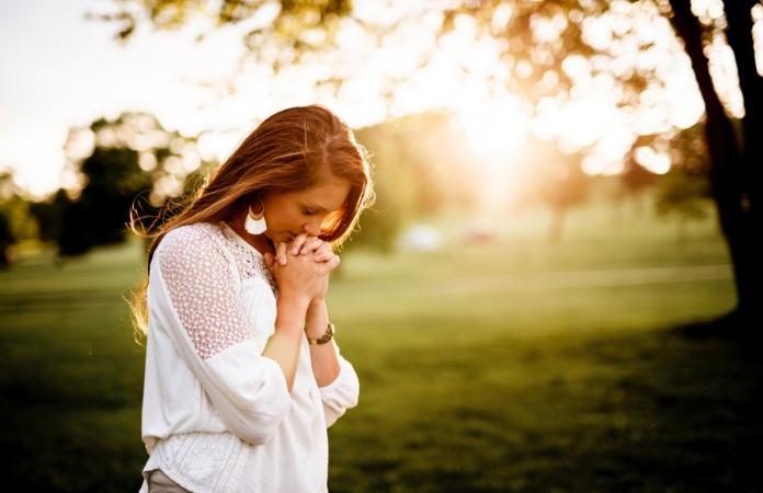 Woman in nature praying